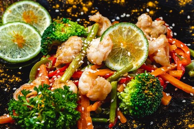 Vista laterale mescolare le verdure gamberi alla griglia con brocoli carota peperone verde fagiolo fette di lime e semi di sesamo su un piatto