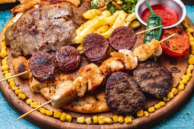 Vista laterale mix di spiedini cotolette di carne alla griglia spiedini di pollo e salsiccia sucuk pepe verde caldo pomodori alla griglia mais dolce e patatine fritte sul pane