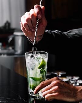 Vista laterale mojito cocktail rum con menta lime e ghiaccio nel bicchiere