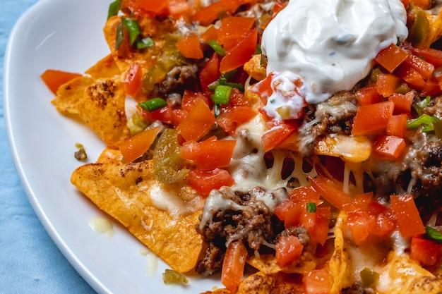 Vista laterale nachos tortilla chips con pepe macinato alla griglia carne macinata di pomodoro primavera formaggio jalapeno pepe e panna acida in cima
