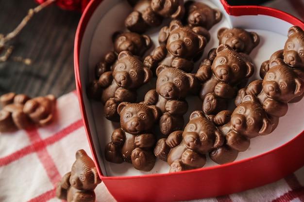Vista laterale orsi di cioccolato in una scatola a forma di cuore rossa