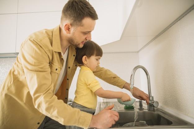 Vista laterale padre e figlio, lavare i piatti