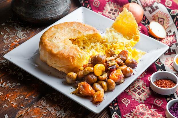 Vista laterale pilaf in una pita con castagne, albicocche secche, ciliegia susina. piatto orientale tradizionale su una superficie di legno scuro orizzontale
