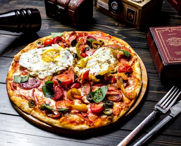Vista laterale pizza mista con pomodori olive peperone uova salsicce a bordo un libro un coltello e una forchetta sul tavolo