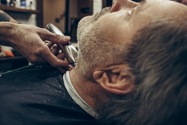 Vista laterale posteriore del primo piano uomo caucasico barbuto senior bello che ottiene governare barba nel barbiere moderno.