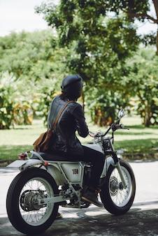 Vista laterale posteriore dell'uomo irriconoscibile in sella a bici in una giornata di sole