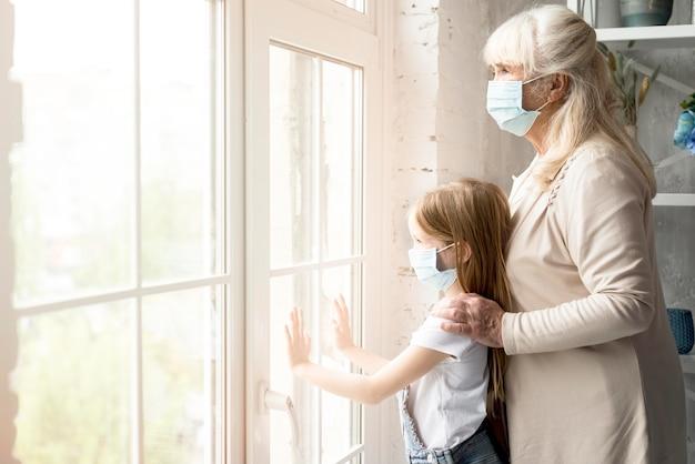 Vista laterale ragazza e nonna con maschera