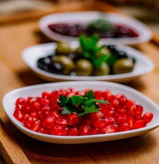 Vista laterale snack melograno olive nere e verdi e salsa sul tavolo