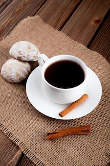 Vista laterale tazza di caffè con cannella e pan di zenzero sul tavolo di legno