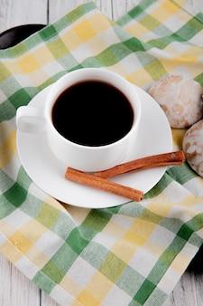 Vista laterale tazza di caffè con cannella e pan di zenzero sulla tovaglia