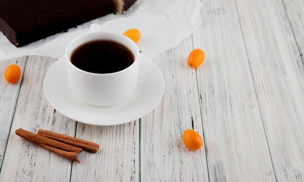 Vista laterale tazza di caffè con kumquat alla cannella e torta di cialde croccante sul tavolo di legno bianco
