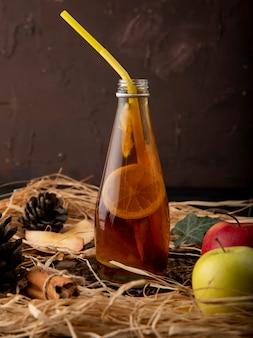 Vista laterale tè al limone con calce cannella edera foglia abete cono mele rosse e verdi sulla paglia