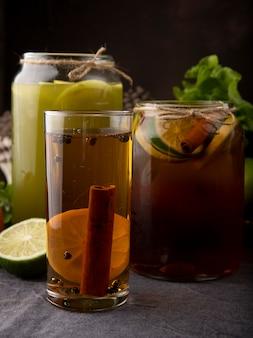Vista laterale tè freddo al limone con succo di mela fresco alla cannella e fetta di lime