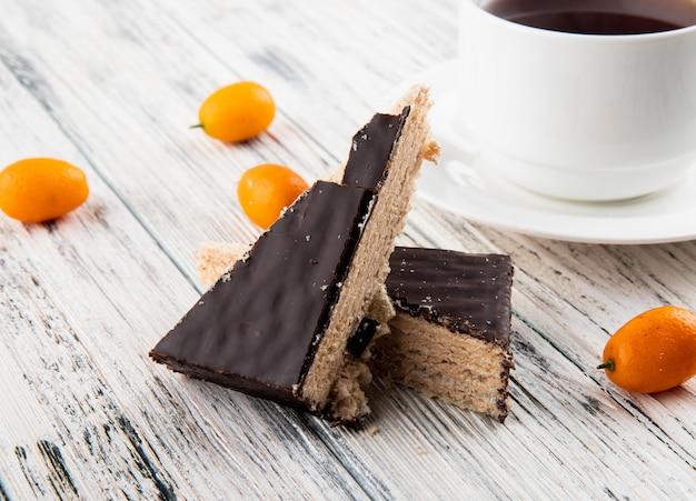Vista laterale torta di cialde croccante con una tazza di tè nero e kumquat sul tavolo di legno bianco