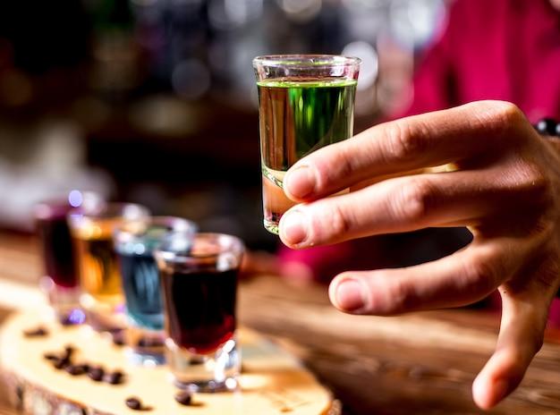 Vista laterale un uomo beve colpi colorati con chicchi di caffè su un pezzo di legno
