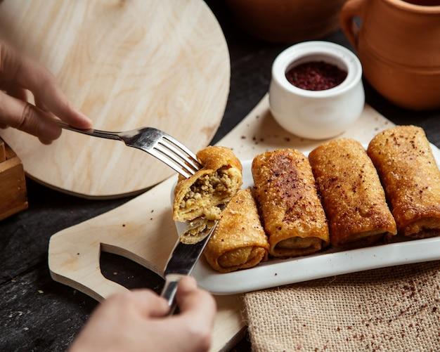 Vista laterale una ragazza mangia pancake arrotolati con carne cosparsa di sumac su una tavola