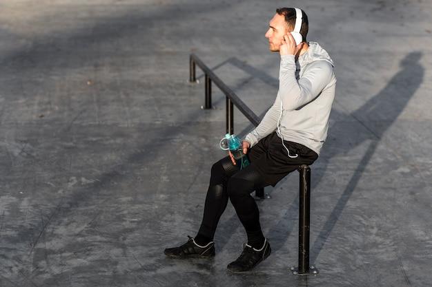 Vista laterale uomo ascolto musica e tenendo una bottiglia d'acqua