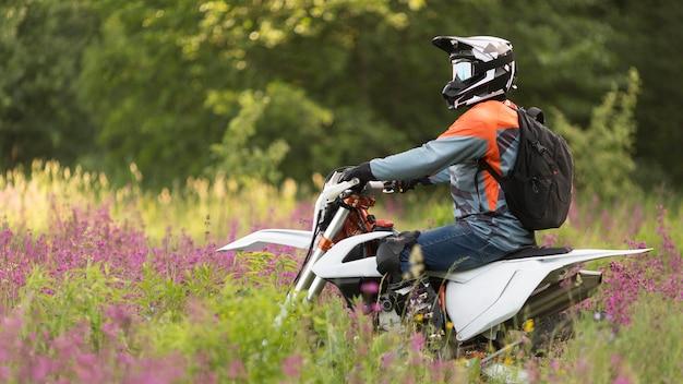 Vista laterale uomo attivo in sella a una moto nella foresta