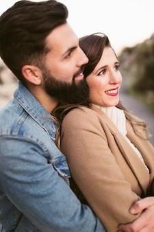 Vista laterale uomo che abbraccia la donna e guardando lontano