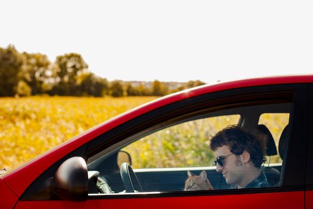 Vista laterale uomo che tiene un gatto in macchina