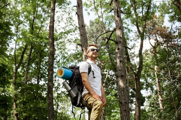 Vista laterale uomo con zaino nella foresta