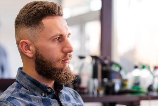Vista laterale uomo in attesa di un taglio di capelli