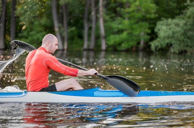Vista laterale uomo in kayak con pagaia