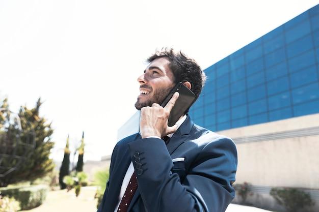 Vista laterale uomo in tuta parlando al telefono