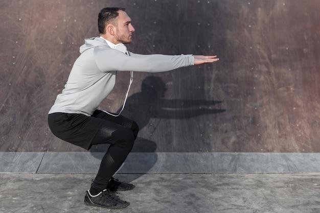 Vista laterale uomo sportivo facendo squat