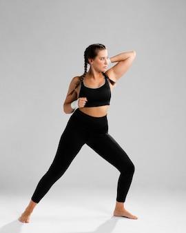 Vista lunga della donna che osserva via ed esercizio fisico