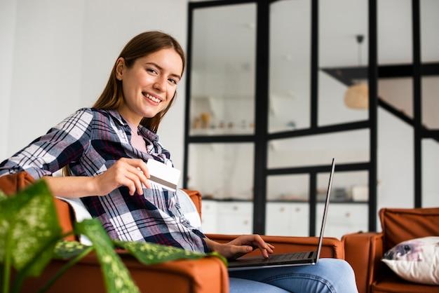 Vista lunga della donna che si siede e che esamina macchina fotografica