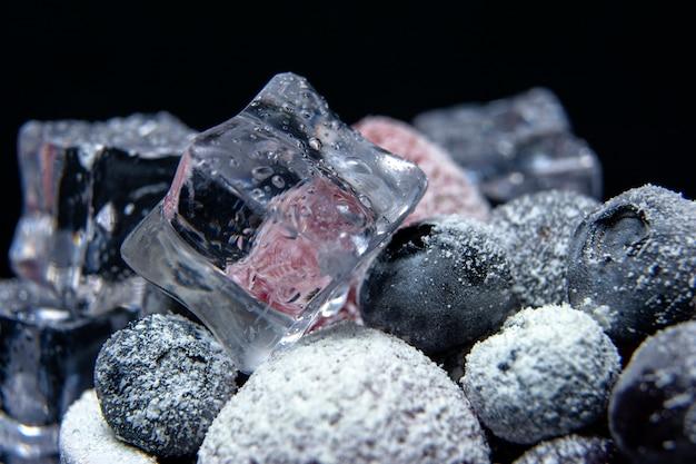 Vista macro di frutti di bosco congelati: fragola, mirtillo con cubetti di ghiaccio su sfondo scuro