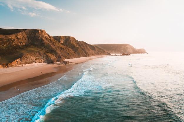 Vista mozzafiato sull'oceano e sulle scogliere rocciose sotto il bellissimo cielo luminoso