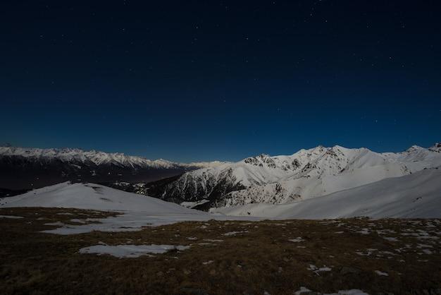 Vista notturna del cielo stellato sulle alpi. catena montuosa innevata al chiaro di luna.