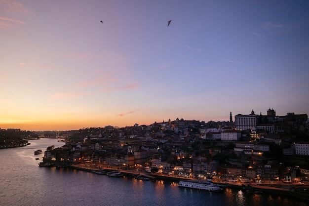 Vista notturna del fiume douro con barche. punto di riferimento europeo. stile di vita di viaggio.