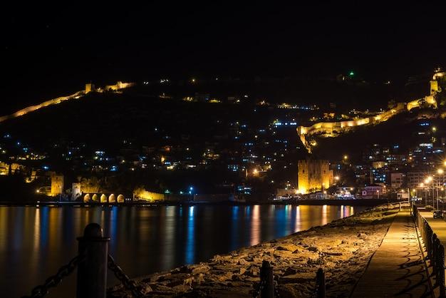Vista notturna del porto, fortezza e antico cantiere navale di alanya, turchia.