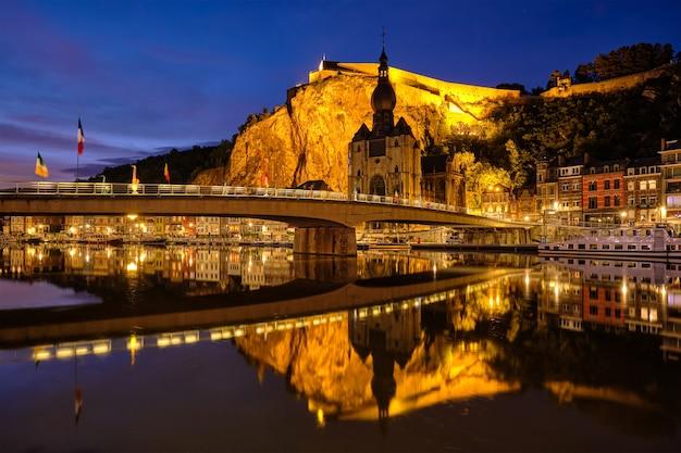 Vista notturna della città di dinant, la chiesa collegiata di notre dame de dinant sul fiume mosa e il ponte pont charles de gaulle e la cittadella di dinant illuminata di sera. dinant, belgio