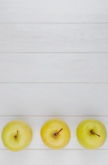Vista orizzontale delle mele verdi su superficie di legno con lo spazio della copia