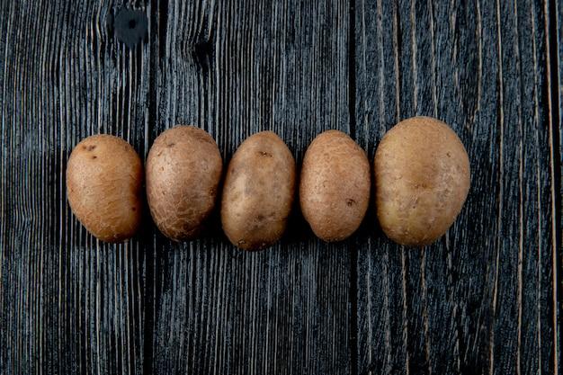 Vista orizzontale delle patate su fondo di legno con lo spazio 3 della copia