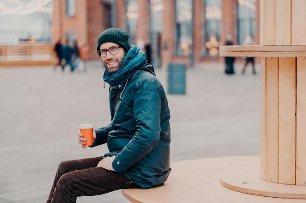 Vista orizzontale di allegro uomo europeo con setola spessa, indossa cappello e giacca