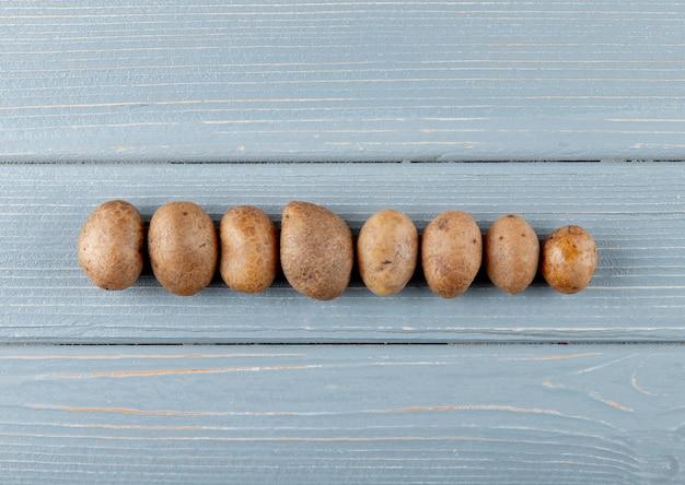 Vista orizzontale di intere patate su fondo di legno con lo spazio della copia
