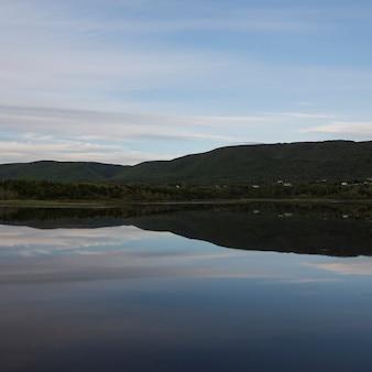 Vista panoramica del fiume calmo con le montagne sullo sfondo, cheticamp, cabot trail, isola di cape breton,