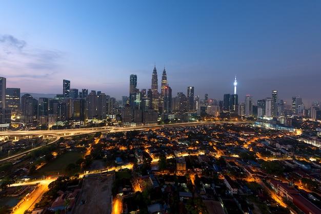Vista panoramica dell'orizzonte della città di kuala lumpur durante i grattacieli di osservazione di alba che costruiscono in malesia.