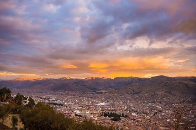 Vista panoramica della città di cusco con cloudscape incandescente e cielo colorato al crepuscolo. cusco è tra le destinazioni di viaggio più importanti in perù e in tutto il sud america.