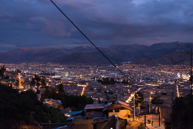 Vista panoramica della città di cusco con luci della città incandescente al crepuscolo. cusco è tra le destinazioni di viaggio più turistiche in perù e sud america.