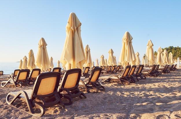 Vista panoramica della spiaggia sabbiosa privata con lettini e ombrelloni sul mare e sulle montagne. ricorrere.
