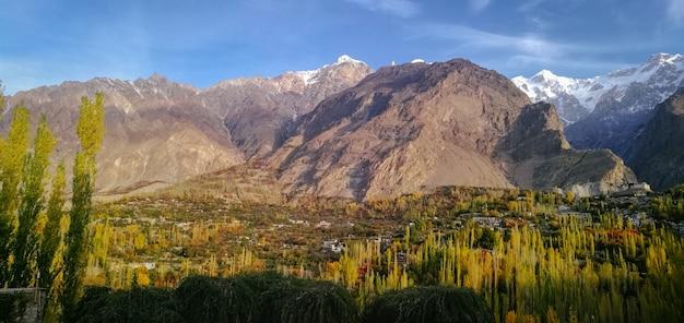 Vista panoramica della valle di hunza in autunno con la neve ricoperta della montagna di ultar sar nella gamma di karakoram.
