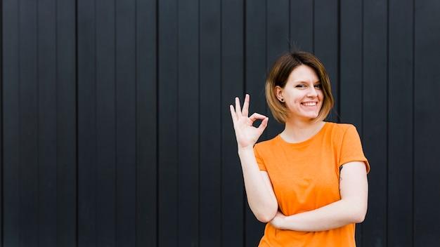 Vista panoramica di un ritratto sorridente di una giovane donna che mostra segno giusto
