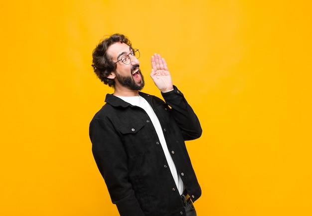 Vista pazza di profilo del giovane uomo bello, sembrante felice ed eccitata, gridando e chiamando per copiare spazio dal lato sopra la parete arancio