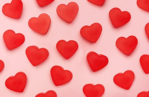 Vista piana dei cuori dei biglietti di s. valentino su fondo rosa